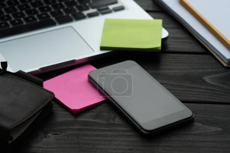 Smartphone, sticky notes and laptop