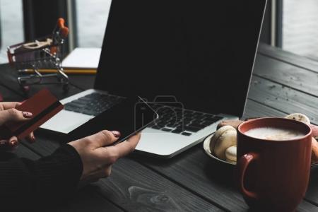 Foto de Recortar vista de mujer en smartphone, laptop y tarjeta de crédito, tienda de café - Imagen libre de derechos