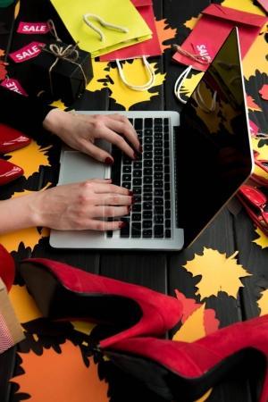 Photo pour Recadrée vue des mains de femme avec ordinateur portable sur une table en bois avec leurs feuilles de papier, talons et étiquettes de vente - image libre de droit