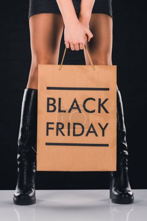 Photo for Cropped view of woman holding shopping bag with black friday sign, isolated on black - Royalty Free Image