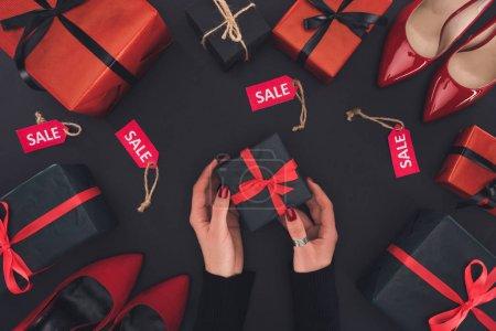 Photo pour Vue recadrée de femme tenant la boîte-cadeau, isolée sur fond noir avec des cadeaux, des talons et des étiquettes de vente - image libre de droit
