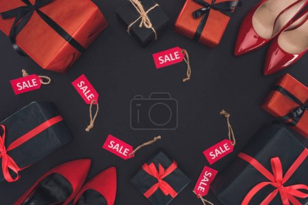 Photo for Flat lay with red heels, presents and sale tags, isolated on black, black friday concept - Royalty Free Image