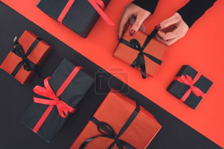 Photo for Cropped view of woman holding gift boxes, on red and black - Royalty Free Image
