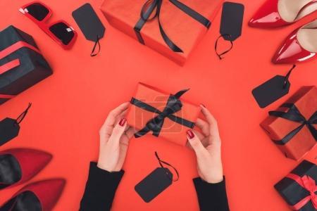 Photo pour Vue recadrée de la femme tenant boîte cadeau, isolé sur rouge avec cadeaux, talons et étiquettes - image libre de droit
