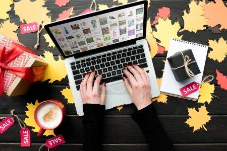 Photo pour Vue du dessus de la femme tapant sur ordinateur portable avec site Web sur table en bois avec feuillage et cadeaux - image libre de droit