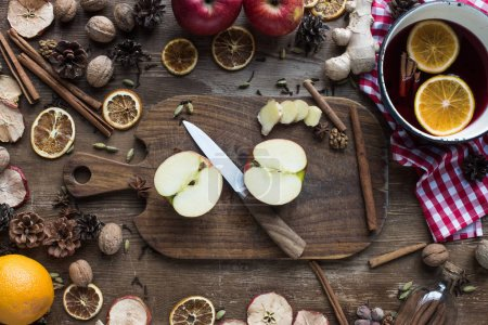 Photo for Top view of cut apple and knife on a wooden board for preparing mulled wine - Royalty Free Image