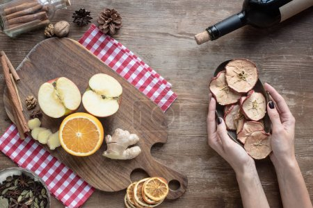 woman putting bowl with dried apples