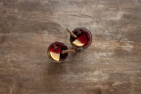 Photo for Top view of two glasses with mulled wine on a wooden table - Royalty Free Image