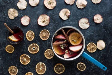 Photo pour Vue du dessus de trempette à eau et verre avec vin chaud fait maison parmi les fruits secs - image libre de droit