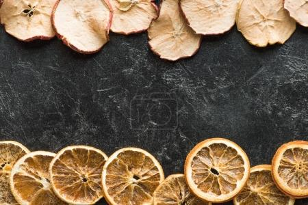 Photo for Top view of dried apples and oranges on a dark grungy surface - Royalty Free Image