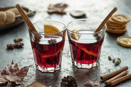 Photo pour Deux verres de vin chaud avec bâtonnets de cannelle sur une surface grise - image libre de droit