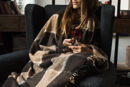 fille assise dans un fauteuil avec du vin chaud