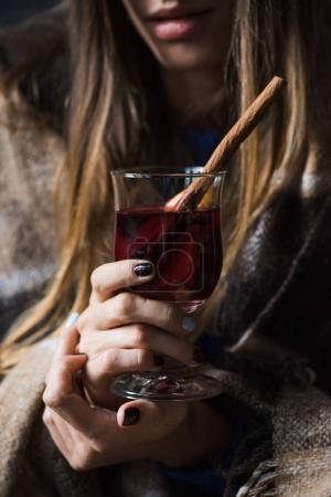 Photo for Cropped image of girl holding glass of mulled wine and sitting wrapped in blanket - Royalty Free Image