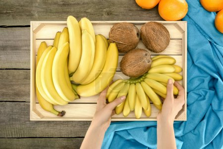 hands with bananas and coconuts