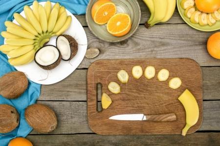 Foto de Vista superior del banano en rodajas con el cuchillo sobre la tabla de cortar y frutas tropicales maduras en mesa - Imagen libre de derechos