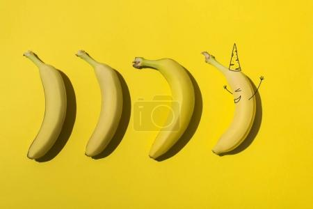 Photo for Ripe fresh bananas and one banana in party hat on yellow - Royalty Free Image