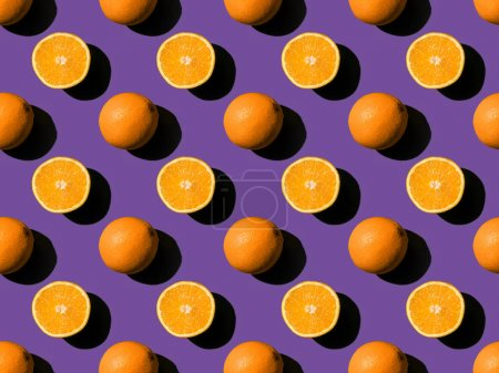 Photo for Top view of ripe fresh whole and halved oranges on purple - Royalty Free Image