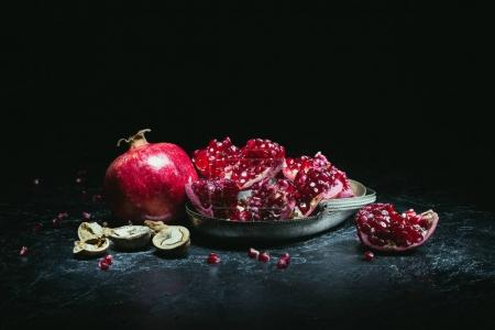 Photo for Pomegranates in metal bowl and walnuts on a table - Royalty Free Image