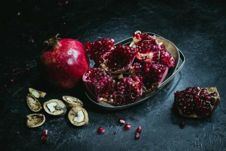 Photo for Overhead view of pomegranates in metal bowl and walnuts on a table - Royalty Free Image