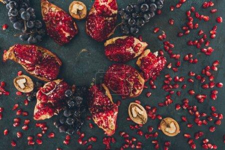 Photo pour Vue de dessus de Grenade avec les raisins et les noix et les graines de Grenade épars - image libre de droit