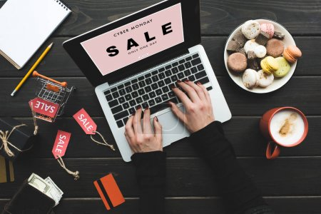 Photo for Cropped view of woman shopping online with credit card and laptop on table with macarons, coffee and sale tags - Royalty Free Image