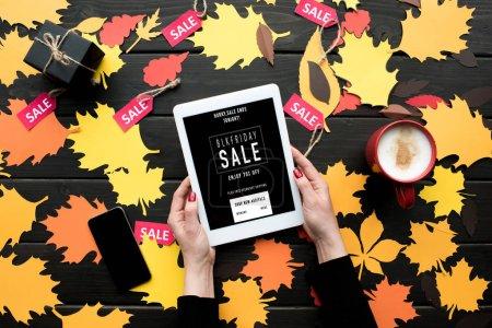 Foto de Vista recortada de las manos femeninas con tableta digital con pantalla en blanco sobre mesa en otoño las hojas, café y venta de etiquetas - Imagen libre de derechos