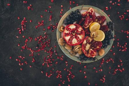 Photo for Top view of plate with pomegranates, grapes and lemons - Royalty Free Image