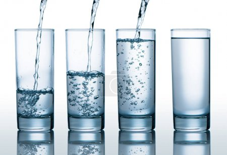 Photo for Transparent glasses with different level of water, pouring water into glasses - Royalty Free Image