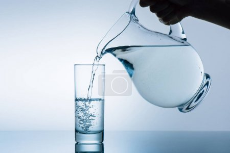 Photo for Cropped image of woman pouring water from jug into glass - Royalty Free Image