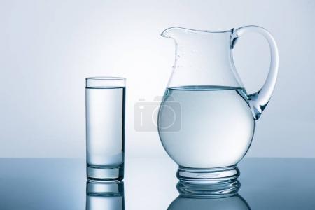 Photo pour Carafe et verre avec de l'eau reflétant la table - image libre de droit