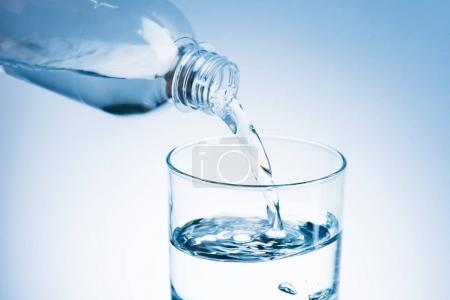 Photo for Pouring water from plastic bottle into glass - Royalty Free Image