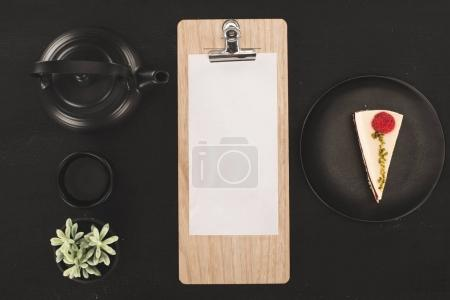Photo for Top view of sheet of paper on clipboard, piece of cake and tea set on black - Royalty Free Image