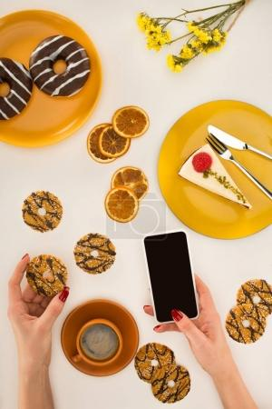 hand with smartphone and cookies