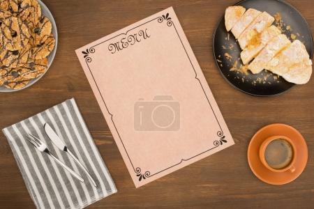 Photo pour Vue de dessus du menu décoratif blanc, tasse de café et de délicieux desserts sur la table en bois - image libre de droit