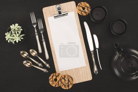 Photo for Top view of blank paper on clipboard, ceramic tea set and cookies on black - Royalty Free Image