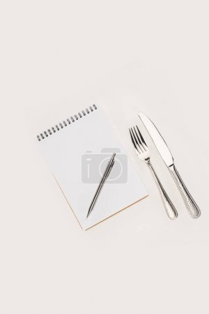 notebook with pen and cutlery