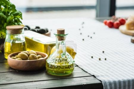 Photo pour Bouteilles d'huile d'olive avec des légumes sur la table en bois - image libre de droit