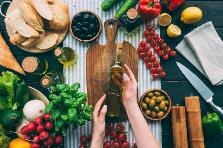 mains tenant la bouteille d'huile d'olive