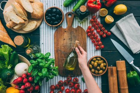 Photo for Top view of cropped hands holding bottle with olive oil on table with vegetables - Royalty Free Image