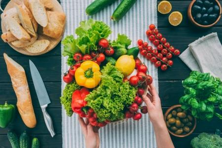 Photo for Top view of cropped hands holding bowl with vegetables on table with towel - Royalty Free Image