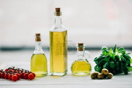 Photo for Olive oil bottles with vegetables on wooden table - Royalty Free Image