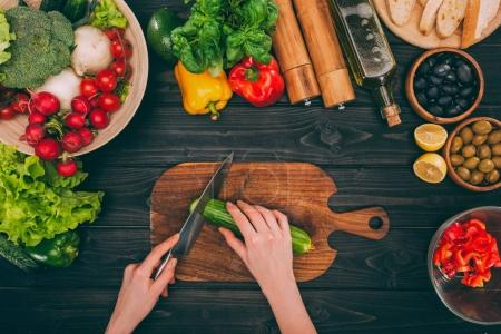 hands slicing cucumber by knife