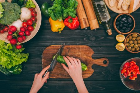 Photo for Top view of cropped hands slicing cucumber by knife on chopping board with vegetables - Royalty Free Image