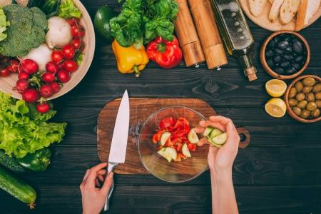 Photo for Top view of cropped hands holding knife and sliced cucumber with vegetables - Royalty Free Image