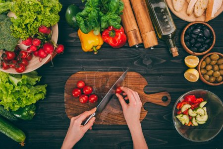 Photo for Top view of cropped hands slicing tomatoes by knife on chopping board with vegetables - Royalty Free Image