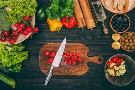 Photo for Top view of sliced tomatoes with knife on chopping board with vegetables - Royalty Free Image