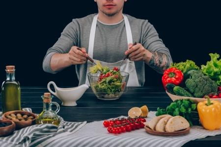 Photo for Man with tattoo mixing ingredients in bowl on table with vegetables - Royalty Free Image