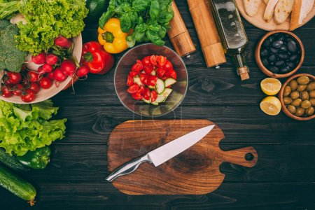 Photo for Top view of chopping board with knife, bowl and vegetables on wooden table - Royalty Free Image