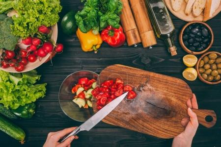hands holding choping board with knife