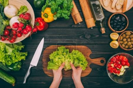 Photo for Top view of cropped hands holding salad leaves on table with vegetables - Royalty Free Image